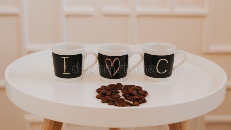 Tres pequeñas tazas de café idénticas en fila que se colocan en la tabla de madera redonda blanca Con el texto amo el café imagen de archivo