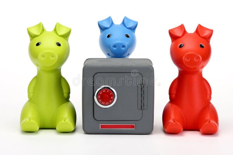 Tres pequeños cerdos que guardan una caja fuerte