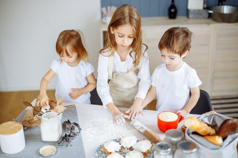 Tres pequeños cocineros que gozan en la cocina que hace lío grande Niños que hacen las galletas en la cocina fotos de archivo libres de regalías