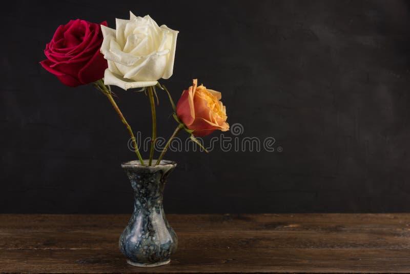 Tres pequeños floreros de mármol con las rosas en negro foto de archivo
