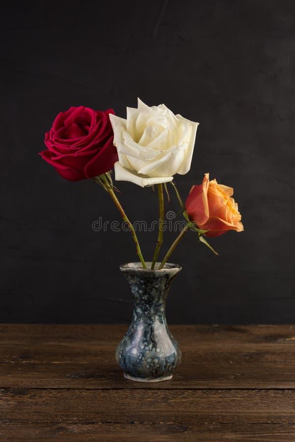 Tres pequeños floreros de mármol con las rosas en negro imágenes de archivo libres de regalías