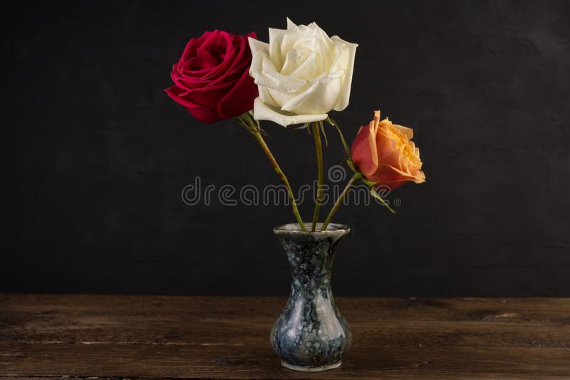Tres pequeños floreros de mármol con las rosas en negro fotos de archivo libres de regalías
