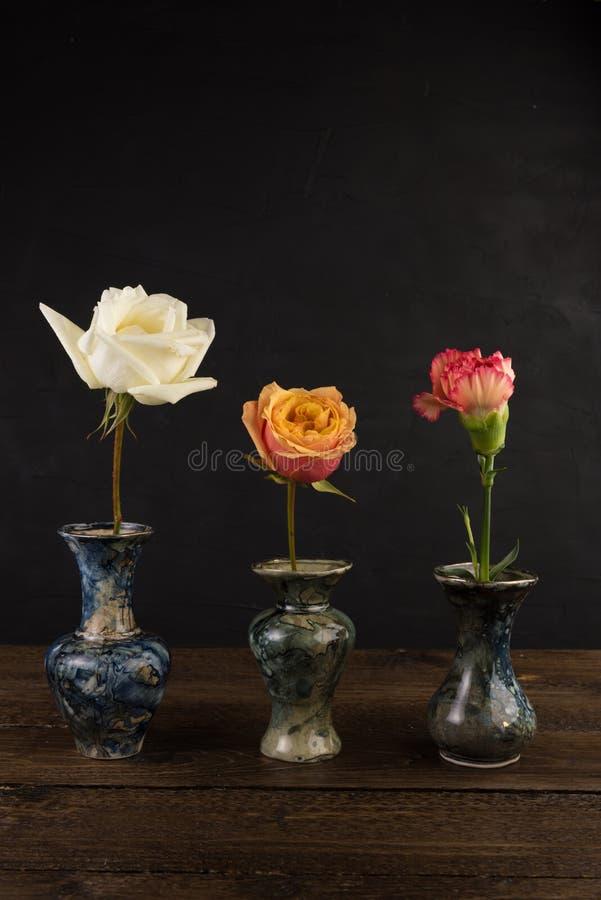 Tres pequeños floreros de mármol con las rosas en negro imagen de archivo libre de regalías