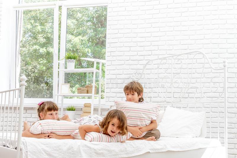 Tres pequeños niños felices que juegan en cama en casa imagenes de archivo