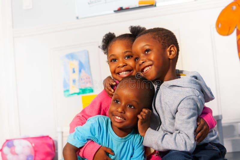 Tres pequeños niños negros felices cierran el abrazo del retrato fotografía de archivo libre de regalías