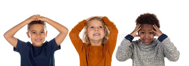 Tres pequeños niños que cubren sus bocas foto de archivo