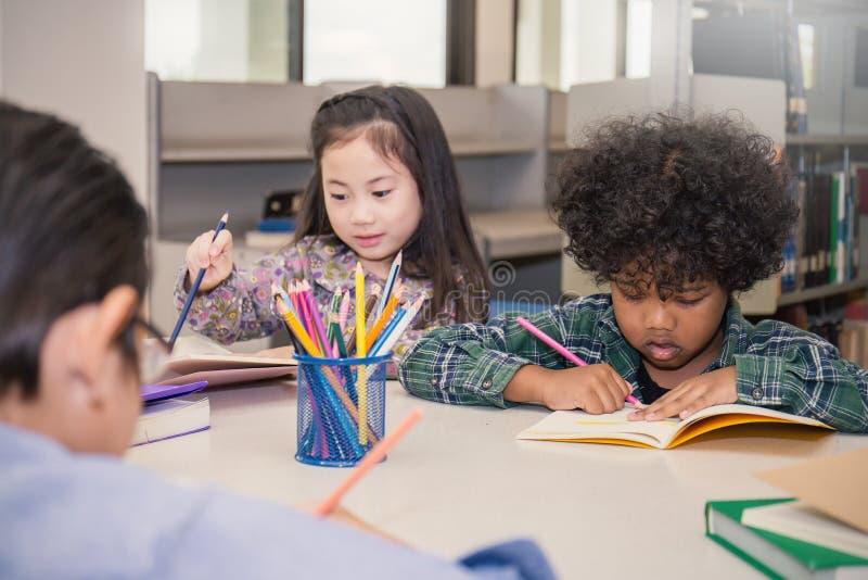 Tres pequeños niños que sientan la mano que sostiene el lápiz y que colorea la imagen imagenes de archivo