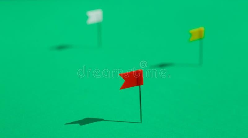 Tres pequeños pernos coloridos de la bandera fijados en una superficie verde Concepto del negocio o del viaje Las metas foto de archivo libre de regalías