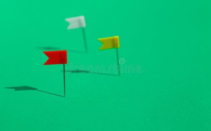 Tres pequeños pernos coloridos de la bandera fijados en una superficie verde Concepto del negocio o del viaje Las metas imagen de archivo libre de regalías
