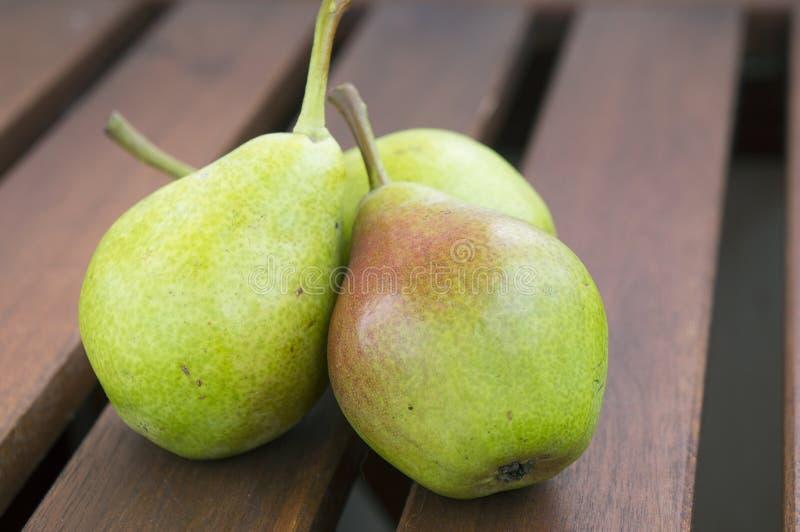 Tres peras verdes orgánicas frescas en una tabla rústica de madera foto de archivo libre de regalías
