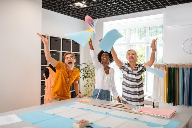 Tres personas creativas alegres que se colocan en un estudio imágenes de archivo libres de regalías