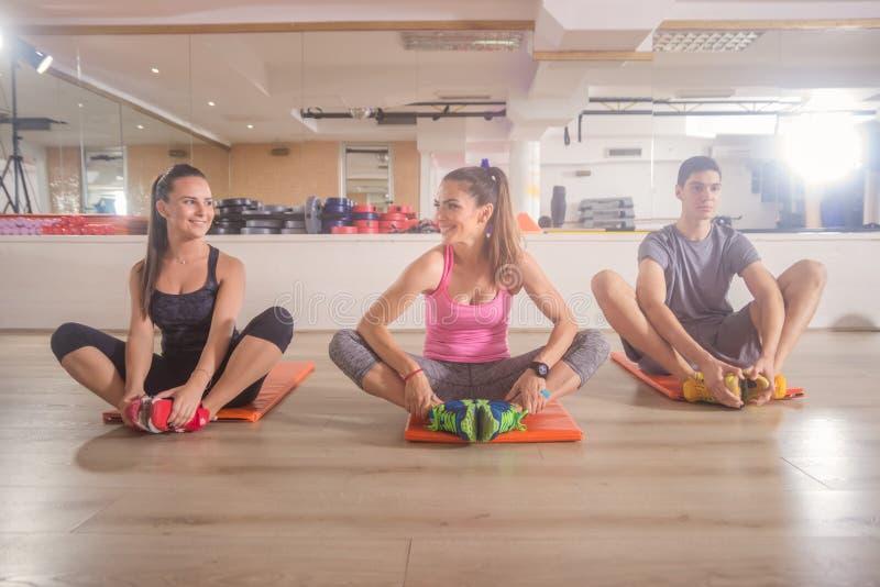Tres personas jovenes agrupan la estera que se sienta de relajación del gimnasio de la aptitud fotos de archivo libres de regalías