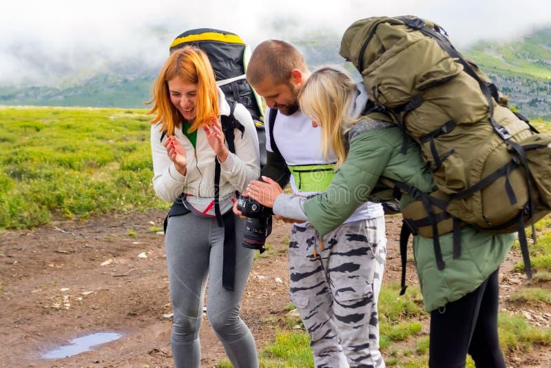 Tres personas jovenes de los amigos de los turistas un muchacho y dos muchachas rubios imágenes de archivo libres de regalías