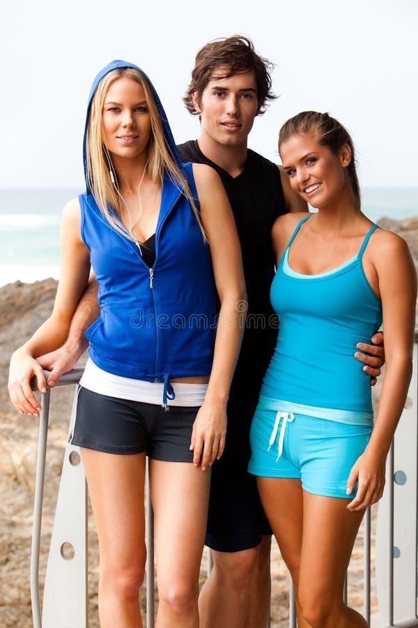 Tres personas jovenes en la playa imagenes de archivo