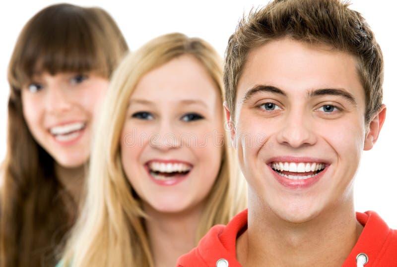 Tres personas jovenes en una fila fotos de archivo