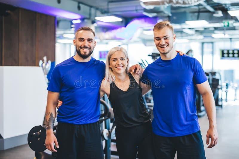 Tres personas jovenes felices que se colocan en el gimnasio foto de archivo libre de regalías
