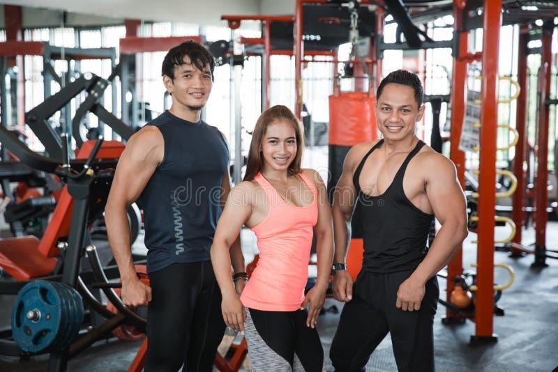 Tres personas jovenes que presentan en gimnasio imagen de archivo