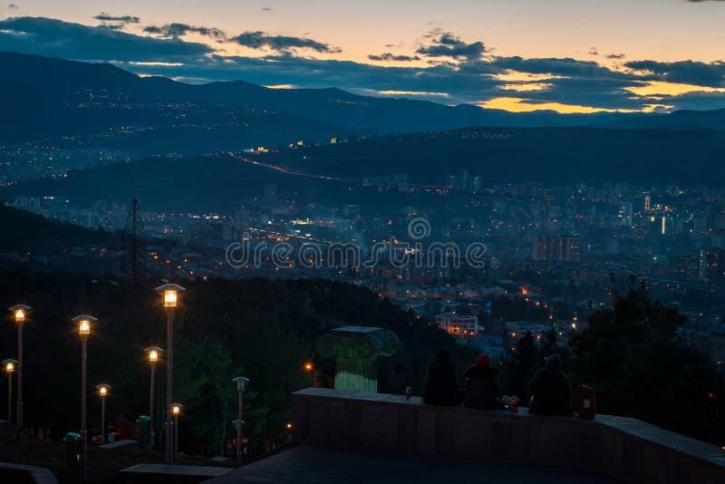 Tres personas jovenes que se sientan encima de la colina que pasa por alto la capital de Georgia, Tbilisi mientras que el sol va  fotografía de archivo