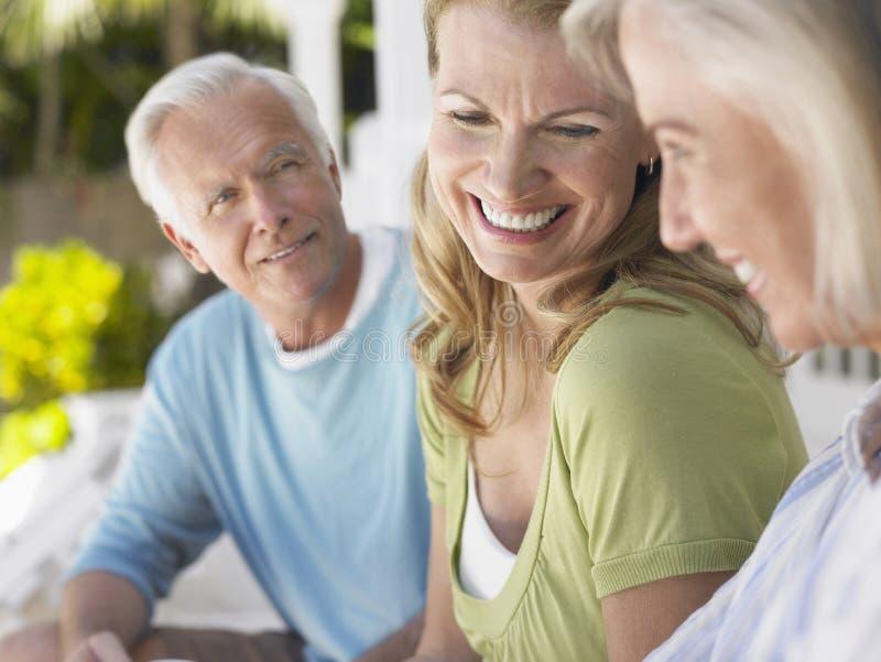 Tres personas maduras felices que se sientan en el mirador foto de archivo libre de regalías