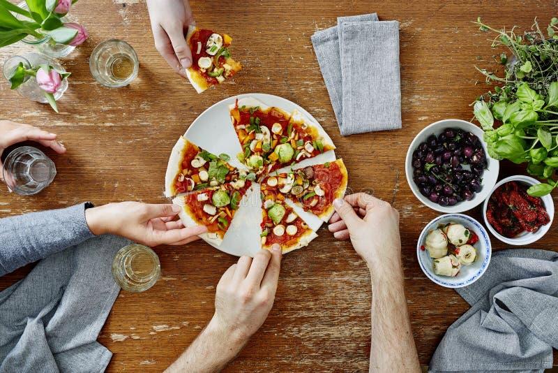Tres personas que comparten la pizza deliciosa orgánica en el partido de cena fotografía de archivo libre de regalías
