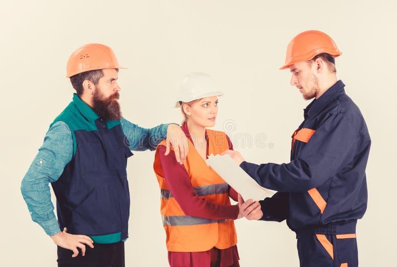 Tres personas que discuten sobre plan, constructores, ingenieros foto de archivo