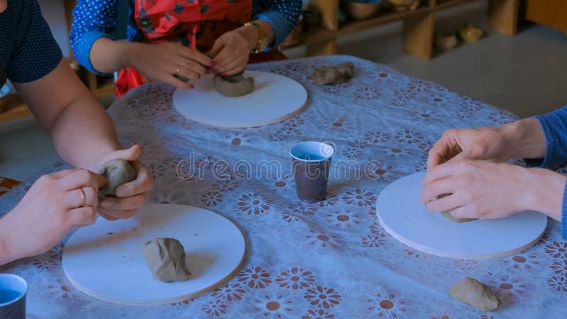 Tres personas que hacen las tazas de la arcilla en estudio de la cer?mica foto de archivo libre de regalías