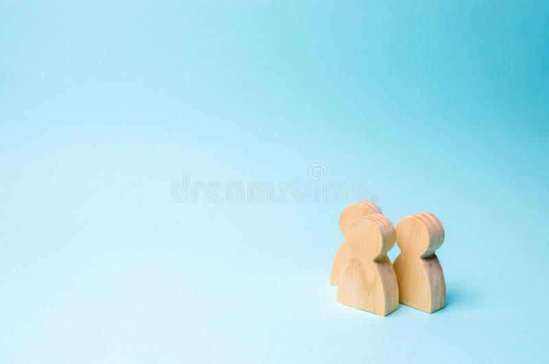 Tres personas se unen y hablan Dos figuras de madera de la gente conducen una conversación sobre un fondo azul comunicación, imagen de archivo libre de regalías