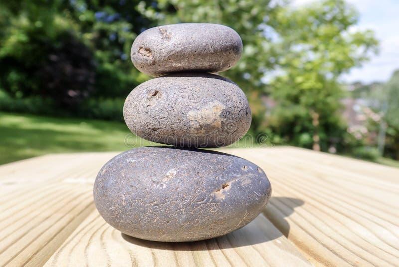 Tres piedras llenadas en superficie de madera de pino imagenes de archivo