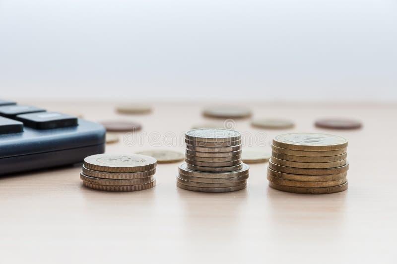 Tres pilas de monedas y una calculadora están en la tabla foto de archivo libre de regalías