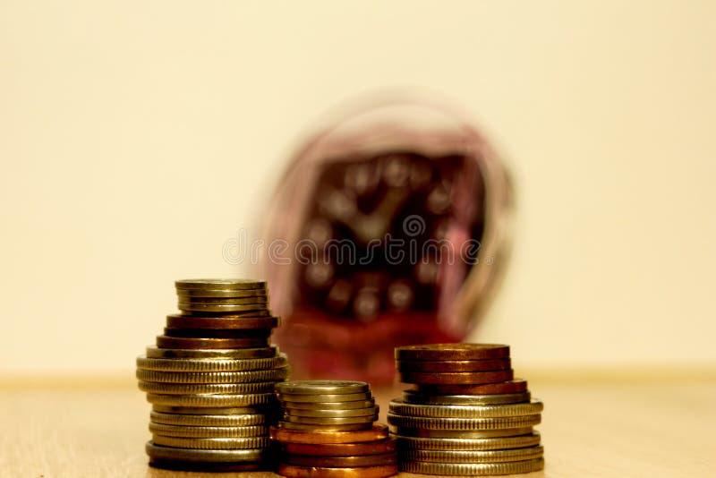Tres pilas desiguales de monedas mienten delante de un despertador fotos de archivo