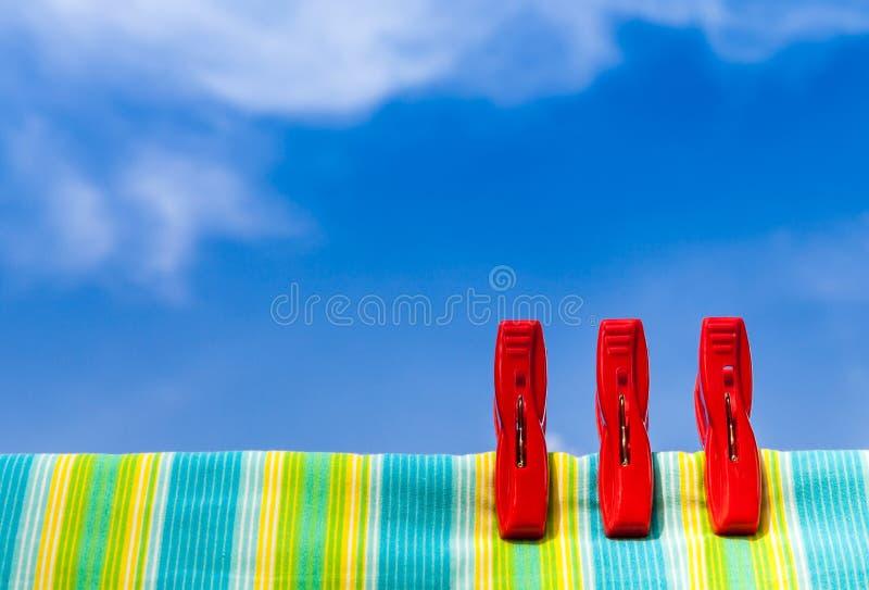 Tres pinzas plásticas rojas y algodón multicolor con el azul fotografía de archivo libre de regalías