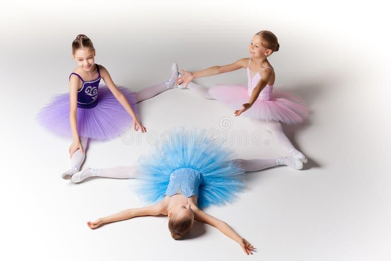 Tres pocas muchachas del ballet que se sientan en tutú y que presentan junto imágenes de archivo libres de regalías