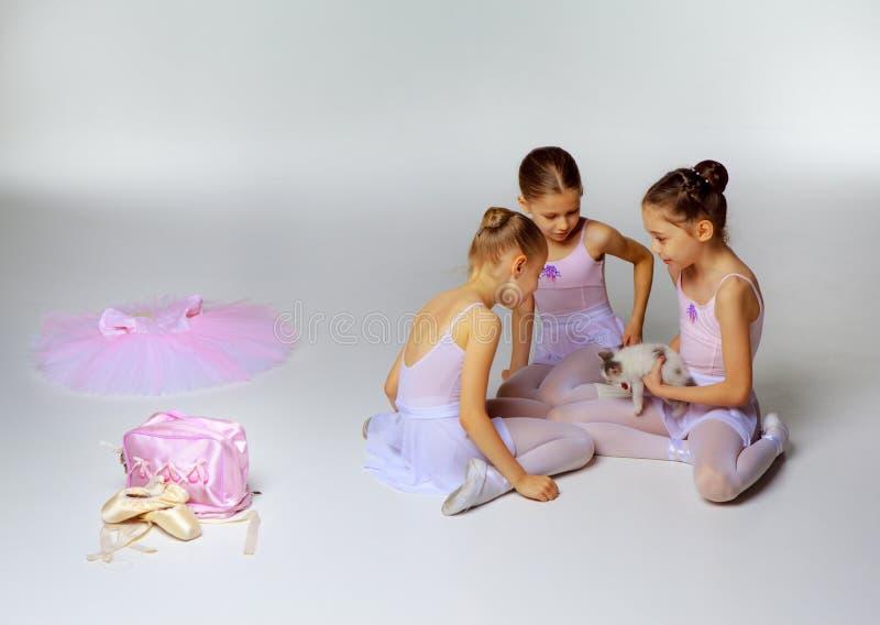 Tres pocas muchachas del ballet que se sientan en tutúes y fotos de archivo libres de regalías