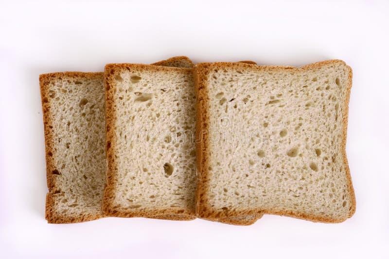 Tres rebanadas de pan blanco en una tabla ligera imagen de archivo libre de regalías