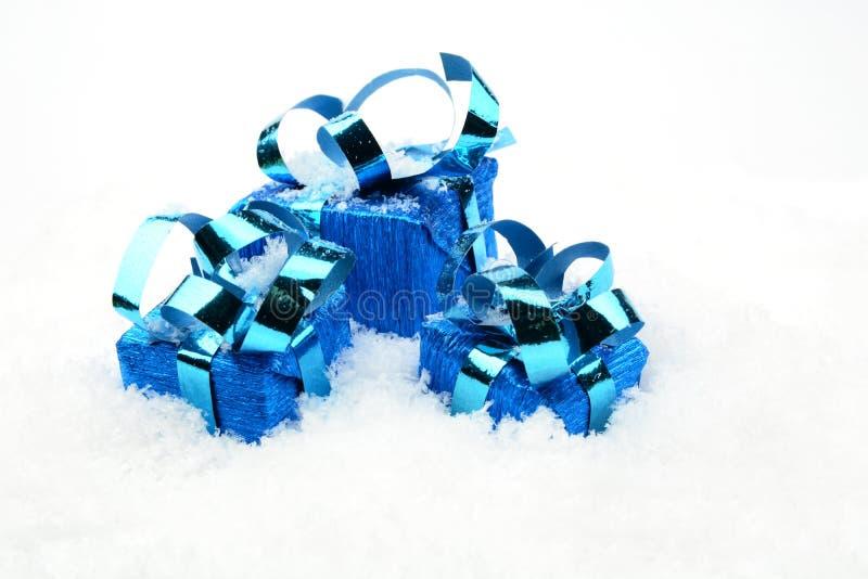 Tres regalos azules de la Navidad en nieve imagen de archivo