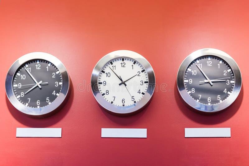Tres relojes en la pared roja que muestra momento diferente imágenes de archivo libres de regalías