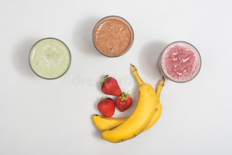 Tres sacudidas del smoothie con los plátanos y las fresas imagenes de archivo