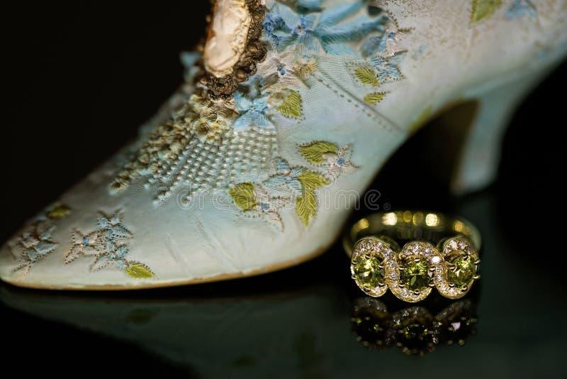 Tres Sapphire Ring Beside Miniature Shoe verde de piedra fotos de archivo