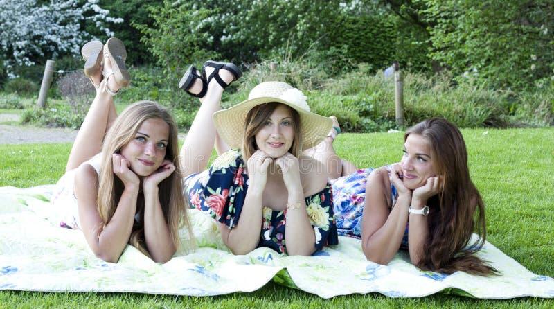 Tres señoras en comida campestre Colocación en la manta imagenes de archivo