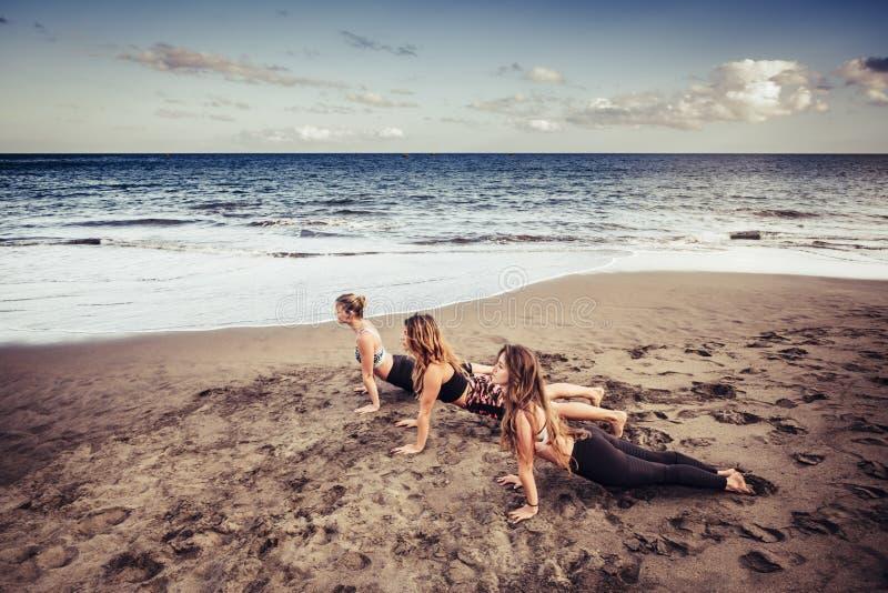 Tres señoras jovenes cacuasian que hacen pilates en la orilla cerca de las ondas y del océano deporte al aire libre del pasatiemp fotos de archivo libres de regalías