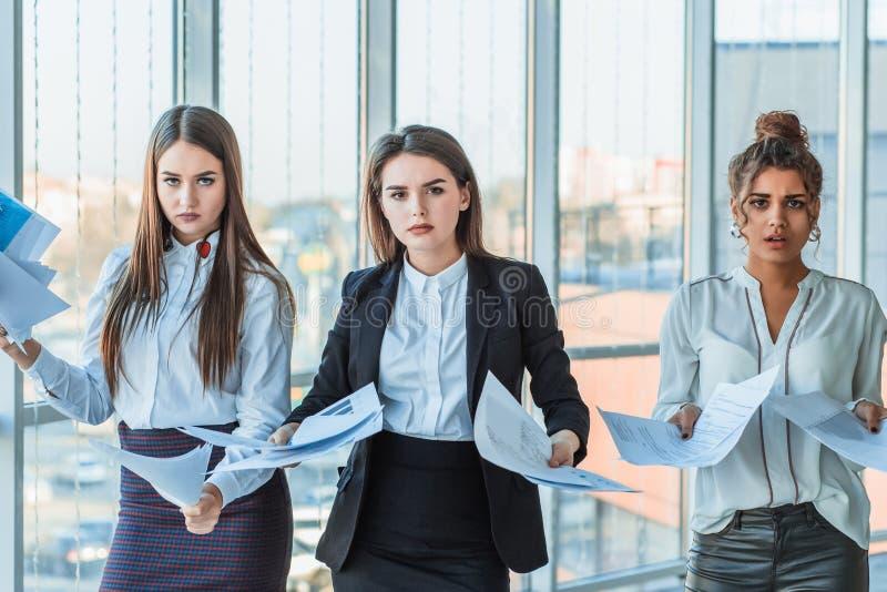 Tres señoras morenas hermosas jovenes del negocio en la oficina Todo el serio, hablando con uno a foto de archivo