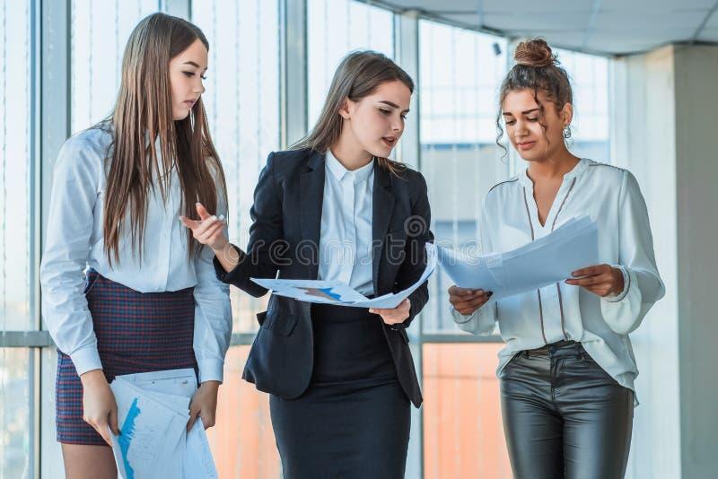 Tres señoras morenas hermosas jovenes del negocio en la oficina Todo el serio, hablando con uno a imagen de archivo