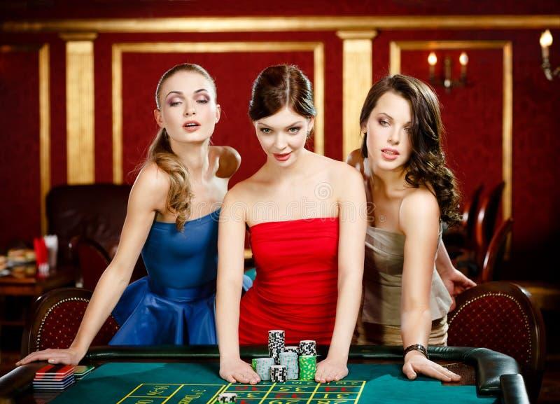 Tres señoras ponen una apuesta que juega la ruleta foto de archivo