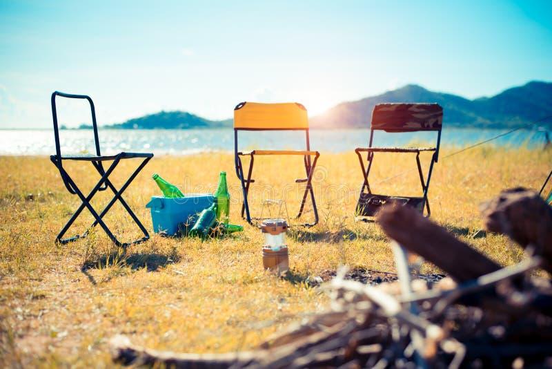 Tres sillas de la comida campestre en el campo del prado Hoguera en primero plano y lago con la monta?a en fondo El acampar y el  foto de archivo libre de regalías