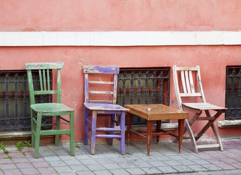 Tres sillas multicoloras viejas se colocan cerca de una pared rosada, fotos de archivo