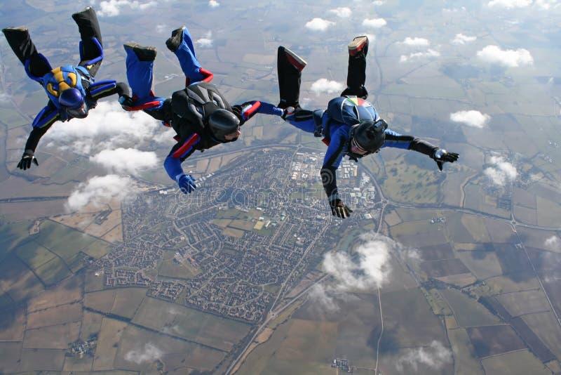 Tres skydivers en una línea detrás de uno a imagen de archivo libre de regalías