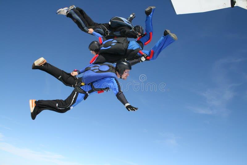 Tres skydivers saltan de un plano imagen de archivo