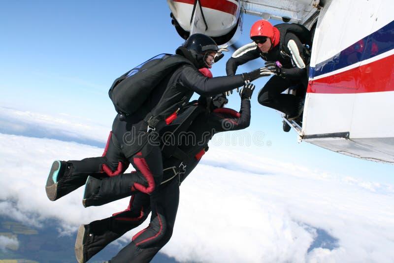 Tres skydivers saltan de un plano imagen de archivo libre de regalías