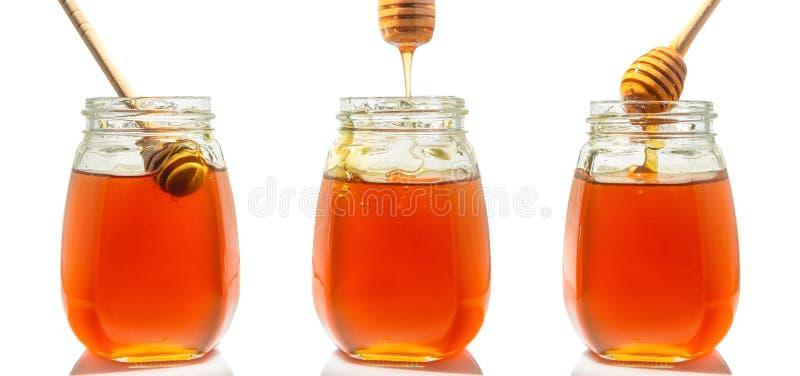 tres tarros de cristal con la miel y las cucharas de madera para la miel fotos de archivo