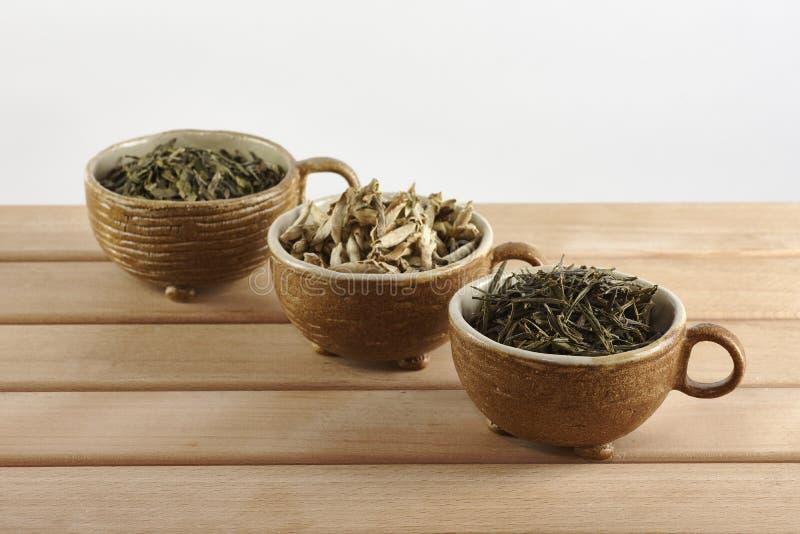 Tres tazas con las hojas de té verdes en un fondo blanco imagenes de archivo